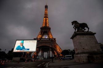 A portrait of a nurse who was mobilized during the COVID-19 pandemic and pictures of other representatives of professional groups are displayed during a tribute on a giant screen in front of The Eiffel Tower in Paris on May 10, 2020, on the eve of France's easing of lockdown measures in place for 55 days to curb the spread of the pandemic, caused by the novel coronavirus. (Photo by Thomas SAMSON / AFP) (Photo by THOMAS SAMSON/AFP via Getty Images)