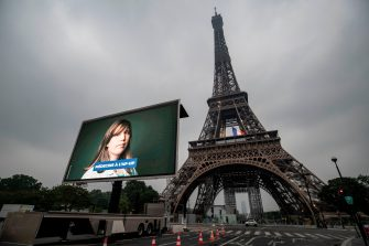 A portrait of a doctor at the AP-HP (Assistance Publique - Hopitaux de Paris) who was mobilized during the COVID-19 pandemic and pictures of other representatives of professional groups are displayed during a tribute on a giant screen in front of The Eiffel Tower in Paris on May 10, 2020, on the eve of France's easing of lockdown measures in place for 55 days to curb the spread of the pandemic, caused by the novel coronavirus. (Photo by Thomas SAMSON / AFP) (Photo by THOMAS SAMSON/AFP via Getty Images)