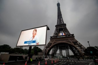 A portrait of a nurse and of other representatives of professional groups who were mobilized during the COVID-19 pandemic are displayed during a tribute on a giant screen in front of The Eiffel Tower in Paris on May 10, 2020, on the eve of France's easing of lockdown measures in place for 55 days to curb the spread of the pandemic, caused by the novel coronavirus. (Photo by Thomas SAMSON / AFP) (Photo by THOMAS SAMSON/AFP via Getty Images)