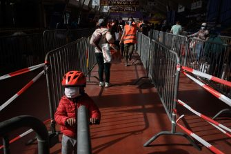 A kid wearing a protective face mask stands with his scooter in a line at a free food distribution for people in need on May 9, 2020 in Geneva as the COVID-19 pandemic casts a spotlight on the usually invisible poor people of Geneva, one of the world's most expensive cities (Photo by Fabrice COFFRINI / AFP) (Photo by FABRICE COFFRINI/AFP via Getty Images)