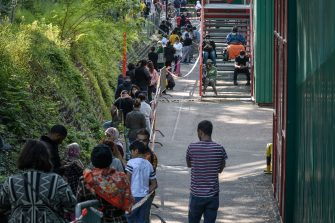 People in need queue at a free food distribution on May 9, 2020 in Geneva as the COVID-19 pandemic casts a spotlight on the usually invisible poor people of Geneva, one of the world's most expensive cities. (Photo by Fabrice COFFRINI / AFP) (Photo by FABRICE COFFRINI/AFP via Getty Images)