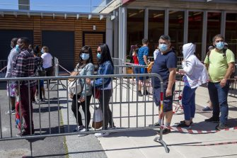 epa08412059 People queue to receive bags with food and essential products received from donations at the ice stadium Les Vernets in Geneva, Switzerland, 09 May 2020 amid the ongoing pandemic of the COVID-19 disease caused by the SARS-CoV-2 coronavirus.  EPA/SALVATORE DI NOLFI