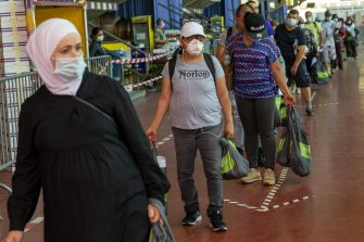 epa08412062 People queue to receive bags with food and essential products received from donations at the ice stadium Les Vernets in Geneva, Switzerland, 09 May 2020 amid the ongoing pandemic of the COVID-19 disease caused by the SARS-CoV-2 coronavirus.  EPA/SALVATORE DI NOLFI