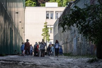 People in need rush to queue for a free food distribution on May 9, 2020 in Geneva as the COVID-19 pandemic casts a spotlight on the usually invisible poor people of Geneva, one of the world's most expensive cities. (Photo by Fabrice COFFRINI / AFP) (Photo by FABRICE COFFRINI/AFP via Getty Images)