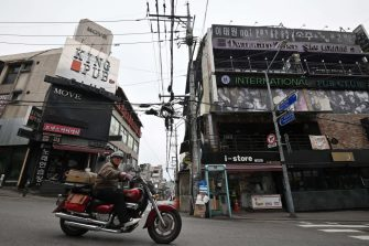 A man rides a motorcycle along a street in the popular nightlife district of Itaewon in Seoul on May 10, 2020. - South Korea's capital has ordered the closure of all clubs and bars after a burst of new cases sparked fears of a second coronavirus wave as President Moon Jae-in urged the public to remain vigilant. (Photo by Jung Yeon-je / AFP) (Photo by JUNG YEON-JE/AFP via Getty Images)