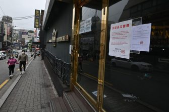 A couple wearing face masks walk past a night club, now closed following a visit by a confirmed COVID-19 coronavirus coronavirus patient, in the popular nightlife district of Itaewon in Seoul on May 10, 2020. - South Korea's capital has ordered the closure of all clubs and bars after a burst of new cases sparked fears of a second coronavirus wave as President Moon Jae-in urged the public to remain vigilant. (Photo by Jung Yeon-je / AFP) (Photo by JUNG YEON-JE/AFP via Getty Images)
