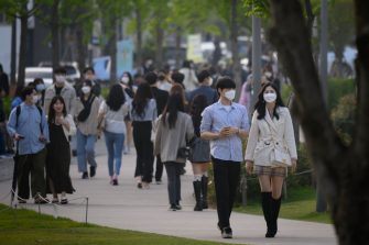 In a photo taken on May 10, 2020, people wearing face masks walk along a street in the Yeonnam district of Seoul. - South Korea announced its highest number of new coronavirus cases for more than a month on May 11, driven by an infection cluster in a Seoul nightlife district just as the country loosens restrictions. (Photo by Ed JONES / AFP) (Photo by ED JONES/AFP via Getty Images)