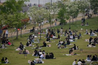 TOPSHOT - In a photo taken on May 10, 2020, people sit in a park in Seoul. - South Korea announced its highest number of new coronavirus cases for more than a month on May 11, driven by an infection cluster in a Seoul nightlife district just as the country loosens restrictions. (Photo by Ed JONES / AFP) (Photo by ED JONES/AFP via Getty Images)