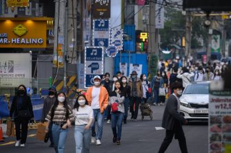 In a photo taken on May 10, 2020, people wearing face masks walk along a street in the Hongdae district of Seoul. - South Korea announced its highest number of new coronavirus cases for more than a month on May 11, driven by an infection cluster in a Seoul nightlife district just as the country loosens restrictions. (Photo by Ed JONES / AFP) (Photo by ED JONES/AFP via Getty Images)