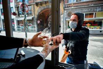A man shops from outside an E-cigarette store in Namur, on May 11, 2020, as Belgium is among other European nations to ease lockdown restrictions today, two months after the World Health Organization declared the COVID-19 pandemic. (Photo by JOHN THYS / AFP) (Photo by JOHN THYS/AFP via Getty Images)