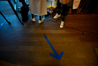 An arrow made with blue tape to mark the circulation direction is pictured on the floor of a store in Namur, on May 11, 2020, as Belgium is among other European nations to ease lockdown restrictions today, two months after the World Health Organization declared the COVID-19 pandemic. (Photo by JOHN THYS / AFP) (Photo by JOHN THYS/AFP via Getty Images)