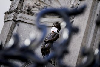 This picture taken on May 11, 2020 in Brussels shows a  face mask set on theManneken-Pis statue  to support the population invited to wear a mask in the public space, on the first day of a partial lifting of the lockdown introduced two months ago to fight the spread of Covid-19 disease caused by the novel coronavirus. (Photo by Kenzo TRIBOUILLARD / AFP) (Photo by KENZO TRIBOUILLARD/AFP via Getty Images)