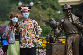 People wearing face masks visit the Disneyland amusement park in Shanghai on May 11, 2020. - Disneyland Shanghai reopened on May 11 to the public after being closed since January due to the COVID-19 coronavirus outbreak. (Photo by Hector RETAMAL / AFP) (Photo by HECTOR RETAMAL/AFP via Getty Images)
