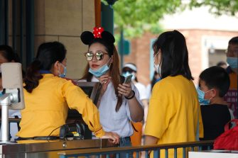 SHANGHAI, CHINA - MAY 11: Visitors have their credentials checked as they enter Shanghai Disneyland after its reopening on May 11, 2020 in Shanghai, China. Shanghai Disneyland has reopened its gates following months of shutdown, offering a potential model for other mass entertainment venues around the world to open for business during the pandemic. (Photo by Hu Chengwei/Getty Images)