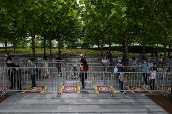 People wearing face mask stand on designated spots to maintain social distancing while waiting to enter the Disneyland amusement park in Shanghai on May 11, 2020. - Disneyland Shanghai reopened on May 11 to the public after being closed since January due to the COVID-19 coronavirus outbreak. (Photo by Hector RETAMAL / AFP) (Photo by HECTOR RETAMAL/AFP via Getty Images)