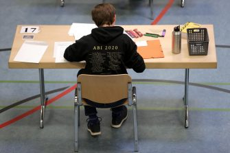 epa08416465 A student writes their final examination paper on biology, in a sports hall, which has been converted into a classroom in accordance with the latest German health regulations, at the Privat High School Stadtkrone (PGS) in Dortmund, Germany, 12 May 2020. Due to the ongoing coronavirus pandemic, the final secondary-school examinations in the German state of North Rhine-Westphalia are starting with strict safety precautions.  EPA/FRIEDEMANN VOGEL