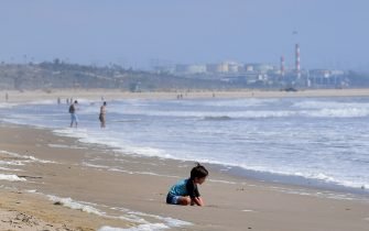 A child plays in the sand at Venice Beach in Venice, California on May 11, 2020 which has remain closed due to the coronavirus pandemic. - Los Angeles County will reopen beaches on Wednesday May 13 to limited active use, requiring social distancing while not allowing for sunbathers or picnics as parking lots will remain closed to help prevent the spread of the coronavirus. (Photo by Frederic J. BROWN / AFP) (Photo by FREDERIC J. BROWN/AFP via Getty Images)