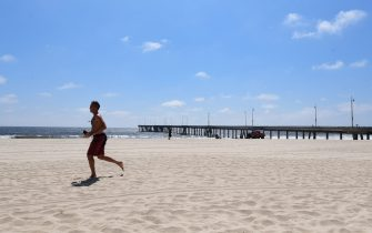 A man jogs on the sand at Venice Beach in Venice, California on May 11, 2020 which has remain closed due to the coronavirus pandemic. - Los Angeles County will reopen beaches on Wednesday May 13 to limited active use, requiring social distancing while not allowing for sunbathers or picnics as parking lots will remain closed to help prevent the spread of the coronavirus. (Photo by Frederic J. BROWN / AFP) (Photo by FREDERIC J. BROWN/AFP via Getty Images)
