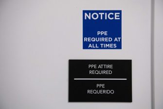 A sign requiring personal protective equipment (PPE) is displayed before entering a temporary field hospital at the Walter E. Convention Center in Washington, DC on May 11, 2020, featuring 437 beds for patients suffering from coronavirus, COVID-19, and part of the city's medical surge response plan as an alternate care site to assist hospitals. (Photo by SAUL LOEB / AFP) (Photo by SAUL LOEB/AFP via Getty Images)