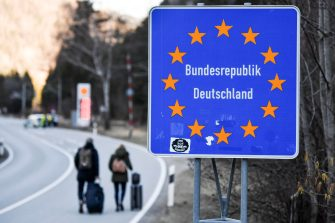 epa08418763 (FILE) - Two people witht their trolley bags walk past a road sign at the border crossing between Germany and Austria in Scharnitz, Germany, 16 March 2020 (reissued 13 May 2020). Media reports state on 13 May 2020 that Germany is planning to partially ease border controls as early as 16 May 2020, following a decision of the Cabinet. At the same time, Austria is planning to reopen the border with Germany as early as 15 June, media added.  EPA/PHILIPP GUELLAND *** Local Caption *** 55955852