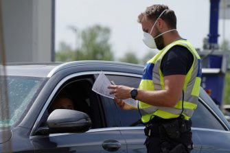 RASTATT, GERMANY - MAY 08: A German border police officers checks the documentation of a driver at a checkpoint of Staustufe Iffezheim B500 road at the German-French border during the coronavirus crisis on May 8, 2020 near Rastatt, Germany. The rates of new infections in both Germany and France, as in much of the European Union, have fallen dramatically over recent weeks, allowing governments to ease lockdown measures and strengthening demands by both business leaders and local communities to reopen international borders. In Germany so far Interior Minister Horst Seehofer is resisting a fast-paced lifting of border closures. (Photo by Thomas Niedermueller/Getty Images)
