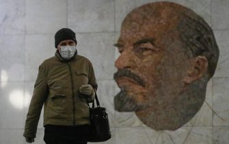 epa08419500 A commuter wearing a face mask and gloves walks in front of a famous mosaic depicting the portrait of Soviet Union founder Vladimir Ilyich Ulyanov (1870-1924)   better known by his nom de guerre, 'Lenin'   created in 1965 by artist Grigory Opryshko at the Biblioteka Imeni Lenina metro station in Moscow, Russia, 13 May 2020. Last week, Moscow Mayor Sergey Sobyanin announced that work would resume at industrial and construction businesses in Moscow starting on 12 May as part of an economic reactivation plan amid the ongoing pandemic of the COVID-19 disease caused by the SARS-CoV-2 coronavirus. Residents of the Russian capital are now required to wear face masks and gloves when using public transport and inside shops. Other restrictions, such as the closure of public parks and general stay-at-home and social distancing guidances, are set to remain in place until 31 May.  EPA/SERGEI ILNITSKY