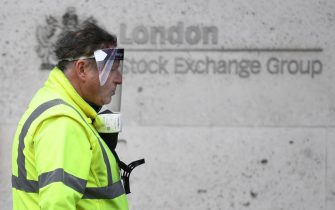 epa08421640 A man wearing a face shield passes a sign outside the London Stock Exchange in the financial district in the City of London, Britain, 14 May 2020. British Chancellor Sunak said it is very likely that the UK is facing a 'significant recession,' reports state. The economy contracted at the fastest pace since the financial crisis in 2008 and shrank by 2 percent in the first three months of 2020, as the ongoing pandemic of the COVID-19 disease caused by the SARS-CoV-2 coronavirus forced the country into lockdown.  EPA/NEIL HALL