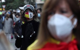 epa08420873 A resident, wearing a face mask picturing a black ribbon and the national flag, attends a protest against the central government for its COVID-19 crisis management in downtown Madrid, Spain, 13 May 2020 (issued 14 May 2020). Several dozen people attended the rally despite the fact that no gatherings are allowed to avoid the spreading of the novel coronavirus disease (COVID-19).  EPA/RODRIGO JIMENEZ