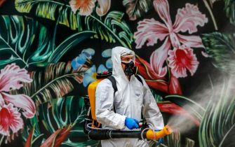 TOPSHOT - An employee wearing protective gear disinfects a shopping mall as a preventive measure against the COVID-19 coronavirus in Caxias do Sul, Brazil on May 13, 2020. (Photo by SILVIO AVILA / AFP)
