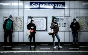 Commuters wearing facemasks wait for a train at the Saint-Laraze platform metro station in Paris on May 14, 2020 during the ease of lockdown measures taken to curb the spread of the COVID-19 (the novel coronavirus). (Photo by Philippe LOPEZ / AFP)