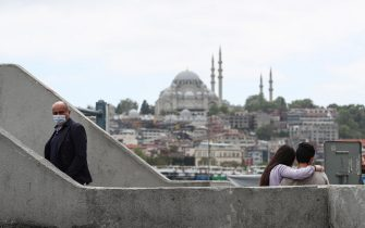 epa08420138 A man wearing face mask walks next to a couple in front of the Suleymaniye Mosque,  amid the ongoing pandemic of the COVID-19 disease caused by the SARS-CoV-2 coronavirus in Istanbul, Turkey, 13 May 2020.  EPA/SEDAT SUNA