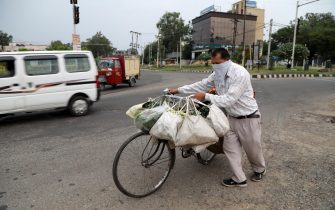 epa08420863 An Indian man sells vegetables on a bicycle during a lockdown to combat the spread of the coronavirus disease (COVID-19) pandemic in Jammu, India, 14 May 2020. Prime Minister of India Narendra Modi has announced a 266 billion US dollar stimulus package in an effort to boost India's economy after it was negativity impacted by the coronavirus outbreak. The dollar value of the rescue package is larger than the gross domestic product (GDP) of 149 countries.  EPA/JAIPAL SINGH