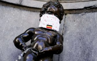 This picture taken on May 11, 2020 in Brussels shows a  face mask set on theManneken-Pis statue  to support the population invited to wear a mask in the public space, on the first day of a partial lifting of the lockdown introduced two months ago to fight the spread of Covid-19 disease caused by the novel coronavirus. (Photo by Kenzo TRIBOUILLARD / AFP)
