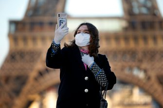 PARIS, FRANCE - MARCH 30: A woman wearing a mask and protective gloves takes a selfie in front of the Eiffel Tower during the Coronavirus epidemic (CODIV 19) on March 30, 2020 in Paris, France. The country is issuing fines for people caught violating its nationwide lockdown measures intended to stop the spread of COVID-19. The pandemic has spread to at least 182 countries, claiming over 30,000 lives and infecting hundreds of thousands more. (Photo by Chesnot/Getty Images)