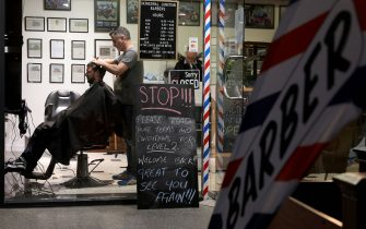 A barber cuts a customer's hair in Christchurch, on May 14, 2020. - New Zealand will phase out its coronavirus lockdown over the next 10 days after successfully containing the virus, although some restrictions will remain, Prime Minister Jacinda Ardern announced on May 11. Ardern said that from May 14 shopping malls, restaurants, cinemas and playgrounds will reopen -- with the country moving to Level Two on its four-tier system. (Photo by Sanka VIDANAGAMA / AFP) (Photo by SANKA VIDANAGAMA/AFP via Getty Images)