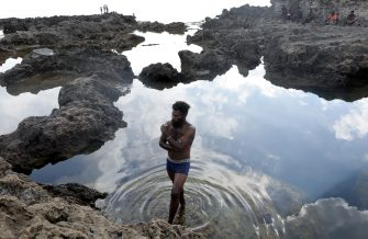 TANNA, VANUATU - DECEMBER 04: A man stands in tide pool on the coast of the Pacific Ocean on December 04, 2019 in Tanna, Vanuatu. The island was hit hard by Cyclone Pam in 2015, a category 5 storm. Scientists have forecast that the strength of South Pacific cyclones will increase because of global warming. (Photo by Mario Tama/Getty Images)