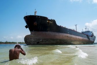 "TOPSHOT - A man takes a swim in the Indian Ocean near the Marshall Islands flagged tanker vessel ""Miracle"" after it ran aground at the mouth of the Dar es Salaam's harbour on February 13, 2016. / AFP / DANIEL HAYDUK        (Photo credit should read DANIEL HAYDUK/AFP via Getty Images)"