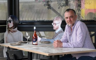 "SYDNEY, AUSTRALIA - MAY 14: Owner of Five Dock Dining, Frank Angeletta sits a table of cardboard cutouts of human beings sitting at tables inside his restaurant on May 14, 2020 in Sydney, Australia. Restaurants and cafes in New South Wales are preparing to reopen with social distancing measures in place as the state government relaxes COVID-19 restrictions.  From Friday 15 May cafes, restaurants and hotel dining areas are allowed to reopen but can only seat 10 patrons at a time and for at least four square metres of space per person. To make patrons feel more comfortable and like they are having a regular dining experience, Five Dock Dining owner Frank Angeletta will use cardboard customers to fill the empty space in his restaurant along with having taped background noise simulating guest ""chatter"" playing for ambience. (Photo by James D. Morgan/Getty Images)"