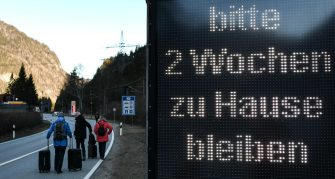 epa08418768 (FILE) - A group of tourists walks past a warning sign reading 'Please stay at home for two weeks', at the border between Germany and Austria, in Scharnitz, Germany, 16 March 2020 (reissued 13 May 2020). Media reports state on 13 May 2020 that Germany is planning to partially ease border controls as early as 16 May 2020, following a decision of the Cabinet. At the same time, Austria is planning to reopen the border with Germany as early as 15 June, media added.  EPA/PHILIPP GUELLAND *** Local Caption *** 55955912