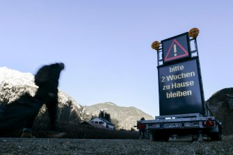 epa08418765 (FILE) - A man walks past a warning sign reading 'Please stay at home for two weeks', at the border between Germany and Austria, in Scharnitz, Germany, 16 March 2020 (reissued 13 May 2020). Media reports state on 13 May 2020 that Germany is planning to partially ease border controls as early as 16 May 2020, following a decision of the Cabinet. At the same time, Austria is planning to reopen the border with Germany as early as 15 June, media added.  EPA/PHILIPP GUELLAND *** Local Caption *** 55955865