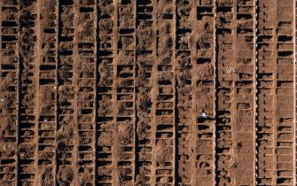 TOPSHOT - Aerial view of a worker of the General Cemetery digging a grave in Santiago May 14, 2020, amid the new coronavirus pandemic. - Health authorities ordered the General Cemetery of Santiago to enable over 1,700 graves under the possibility of an increase in deaths from COVID-19. (Photo by MARTIN BERNETTI / AFP) (Photo by MARTIN BERNETTI/AFP via Getty Images)
