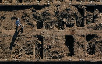 Aerial view of a worker of the General Cemetery digging a grave in Santiago May 14, 2020, amid the new coronavirus pandemic. - Health authorities ordered the General Cemetery of Santiago to enable over 1,700 graves under the possibility of an increase in deaths from COVID-19. (Photo by MARTIN BERNETTI / AFP) (Photo by MARTIN BERNETTI/AFP via Getty Images)