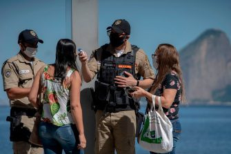 A municipal guard checks the temperature of people that just drop off a bus, during the first day of lockdown due to the COVID-19 coronavirus, at the Icarai neighbourhood in Niteroi, Rio de Janeiro state, Brazil, on May 11, 2020. - Brazil, the hardest-hit Latin American country in the coronavirus pandemic, has surpassed 10,000 deaths, according to figures released last weekend by the Ministry of Health. (Photo by Mauro Pimentel / AFP) (Photo by MAURO PIMENTEL/AFP via Getty Images)