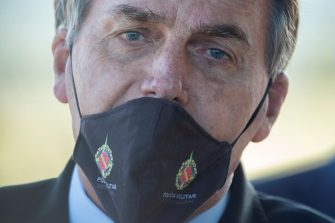 epa08422071 Brazilian President Jair Bolsonaro wearing a face mask with the signage of the Military Police (PM) speaks to press in front of the President's residence Palacio do Alvorada, in Brasilia, Brazil, 14 May 2020. Bolsonaro signed a provisional measure on 14 May 2020 which exempts public officials from responsibility in the 'civil and administrative' spheres in case of mistakes in the fight against the coronavirus.  EPA/Joedson Alves