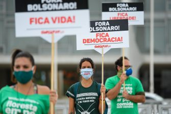 BRASILIA, BRAZIL - MAY 15:Demonstrators wearing face masks and keeping safe distance hold signs against the President of Brazil Jair Bolsonaro and in favor of life, democracy and freedom during a protest amidstthe coronavirus (COVID-19) pandemic in front Planalto Palace on May 15, 2020 in Brasilia. Brazil has over 202,000 confirmed positive cases of Coronavirus and 13,993 deaths. (Photo by Andressa Anholete/Getty Images)