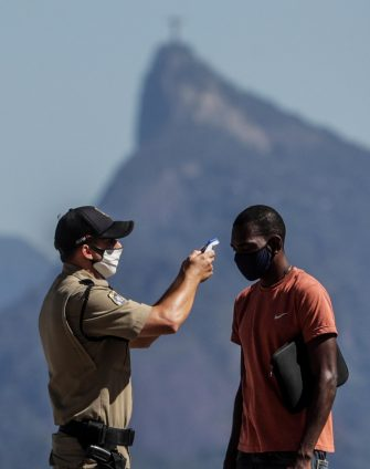 epa08415590 A security officer from the Niterioi city council takes a man's temperature in Niteroi, Rio de Janeiro, Brazil, 11 May 2020. Cities of Niteroi and Sao Gonçalo became the first municipalities in the state of Rio de Janeiro to intensify the restrictive measures of traffic and circulation of people by decreeing the so-called 'lockdown', which will be applied for an initial period of five days. With these two municipalities in the metropolitan region of Rio de Janeiro, there are already twenty Brazilian cities adopting a total blockade to prevent the spread of the pandemic.  EPA/Antonio Lacerda