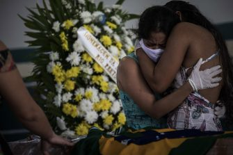 epaselect epa08422921 Indigenous people attend the funeral of the cacique Messias Kokama, 53, a victim of COVID-19, at the Parque de las Tribos in the city of Manaos, Amazonas state, Brazil, 14 May 2020. The cacique Messias Kokama, considered the main indigenous leader of the city of Manaos, capital of the Brazilian state of Amazonas, died a victim of the SARS-CoV-2 coronavirus and his community said goodbye to him this Thursday without being able to pay him all the tributes with their traditional rituals.  EPA/RAPHAEL ALVES