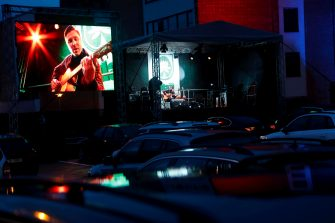 epaselect epa08426868 Latvian musician Marcis Auzins is seen on a huge screen as he performs for a car-bound audience during a Drive-In Concert in Adazi, Latvia, 16 May 2020 evening. People sitting in their cars could enjoy the concert with the sound provided in each car by a special technical solution while keeping the required social distance to others concert goers during the COVID-19 pandemic.  EPA/TOMS KALNINS