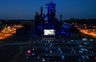 """An aerial view taken on April 17, 2020 shows cars at a newly opened drive-in cinema in front of the  """"Phoenix West"""" former blast furnace in Dortmund, western Germany, amid the novel coronavirus COVID-19 pandemic. (Photo by Ina FASSBENDER / AFP) (Photo by INA FASSBENDER/AFP via Getty Images)"""