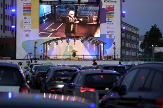 """BONN, GERMANY - MAY 15: German singer Heino performs on stage during the first BonnLive drive-in concert at Am Westwerk during the Coronavirus crisis on May 15, 2020 in Bonn, Germany. The project """"BonnLive Autokonzerte"""" is a series of drive-in concerts with musicians of different genres. The area provides space for about 200 cars. Drive-ins are becoming an increasingly popular venue for singers, theater groups, and even churches to hold events while adhering to Coronavirus lockdown measures. Two peoples are allowed to attend per vehicle and the attendees must remain in their cars. (Photo by Andreas Rentz/Getty Images)"""